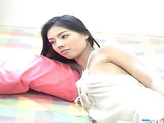 Cute Asian beauty displays her panties in the bedroom